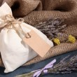 Textile sachet pouch with dried flowers, herbs on wooden table, on sackcloth background — Stock Photo #41515281