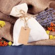 Textile sachet pouch with dried flowers, herbs and berries on wooden table, on sackcloth background — Stock Photo #41515299
