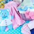 Pile of baby clothes  in basket, on table on color background — Stock Photo #41517511