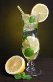 Glass 的鸡尾酒与柠檬和薄荷上暗黄色背景表格 — 图库照片