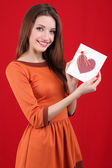 Attractive woman with postcard, on red background — Stock Photo