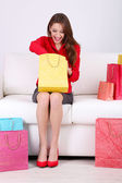 Beautiful young woman sitting on sofa with shopping bags and gift box on gray background — Stock Photo