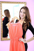 Young beautiful woman trying dress front of mirror in room — Stock Photo