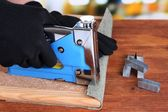 Fastening fabric and board using construction stapler on bright background — Foto Stock