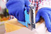 Fastening fabric and wooden box using construction stapler close up — Stok fotoğraf
