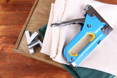 Construction stapler with fabrics and staples on wooden background — Stock Photo
