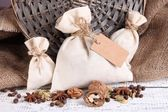 Sacks full with spices, on wooden table, on sackcloth background — ストック写真