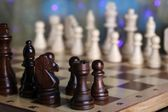 Chess pieces on board on bright background  — Photo