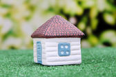 Little house on green grass, on bright background — Стоковое фото