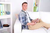 Handsome young man sitting on couch with tablet in room — Stock Photo