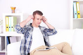 Handsome young man sitting on couch and listening to music in room — Stock Photo