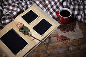 Composition with coffee cup, plaid, and photo album, on wooden background — Stock fotografie