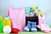 Pilha de roupas de bebê no cesto, na mesa sobre fundo de cor — Fotografia Stock