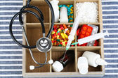 Medical pills,stethoscope,  ampules in wooden box, on color background — 图库照片