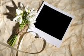 Beautiful bouquet of snowdrops and empty photo paper on old paper background — Foto Stock