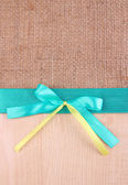 Sackcloth background with color ribbon and bow on wooden board — Stock Photo