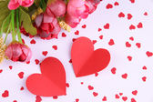 Paper hearts with flowers on bright background — Stok fotoğraf