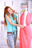 Young girl fashion designer creates new dress in workroom — Stock Photo