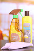 Bottles of furniture polish on wooden table  — Stock Photo