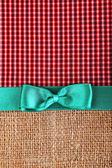 Sac avec ruban couleur et archet sur fond de tissu de couleur — Photo