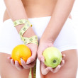 Beautiful young woman with orange, apple and measuring tape isolated on white — Stock Photo #41548859