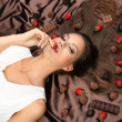 Woman lying on brown atlas covered by chocolate and candies — Stock Photo #41549479