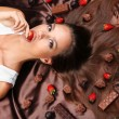 Woman lying on brown atlas covered by chocolate and candies — Stock Photo #41549487