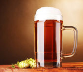 Beer mug and green hop on wooden table on brown background — Stockfoto