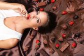 Femme couchée sur atlas brun couvert de chocolat et bonbons — Photo