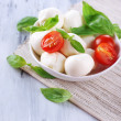 Tasty mozzarella cheese with basil and tomatoes in bowl, on wooden table — Stock Photo #41551181