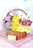 Beautiful chrysanthemum flowers in wicker basket on table on light background  — Foto Stock