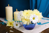 Beautiful chrysanthemum flowers in vase on table on dark blue background — Stock Photo