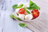 Tasty mozzarella cheese with basil and tomatoes in bowl, on wooden table — Stock Photo