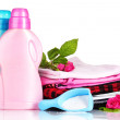 Detergent with washing powder and pile of colorful clothes isolated on white — Stock Photo #41586121