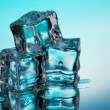 Stock Photo: Melting ice cubes on blue background