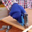 Fastening wooden lath and cork board using construction stapler on bright background — Stok Fotoğraf #41587727