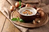 Komposition mit Pilzsuppe in Topf, frische und getrocknete Pilze, auf Holztisch, auf Sackleinen-Hintergrund — Stockfoto