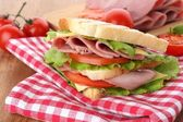 вкусный бутерброд с ветчиной на деревянный стол — Стоковое фото