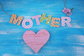 Mother- lettering of handmade paper letters on blue wooden background — Stock Photo