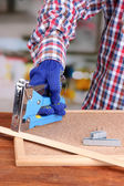 Fastening wooden lath and cork board using construction stapler on bright background — Stock Photo
