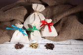 Säckar fulla med kryddor, på träbord, på säckväv bakgrund — Stockfoto