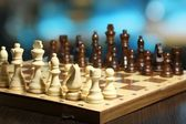 Chess pieces on board on bright background  — Foto Stock
