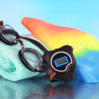Set for pool: swim cap, goggles and towel on blue background — Stock Photo #41684219