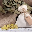 Textile sachet pouch with dried flowers on wooden table, on sackcloth background — Stock Photo #41684471