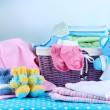 Stock Photo: Pile of baby clothes  in basket, on table on color background