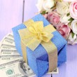 Gift box with money and flowers on color wooden background — Stock Photo #41685883