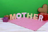Mother- lettering of handmade paper letters on green background — Photo