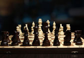 Chess pieces on board on bright background  — Stok fotoğraf