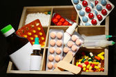 Medical pills, ampules in wooden box, on color wooden background — Photo