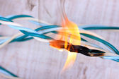 Short circuit, burnt cable, on color wooden background — Stock Photo